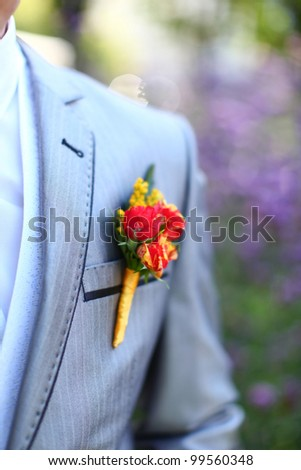 Wonderful wedding boutonniere on a costume of groom from beautiful colorful flowers. Nice bokeh in the background. - stock photo