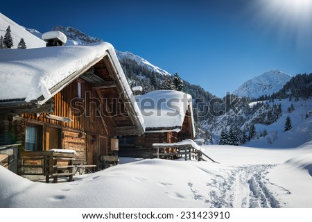 wonderful winter scenery with snow and timber cabin chalet home - stock photo