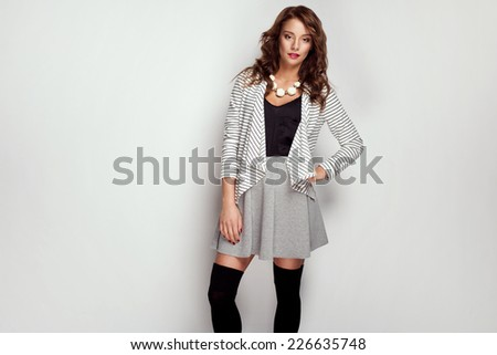 Wonderful young woman in fashionable clothes with long wavy hair looking at camera  - stock photo