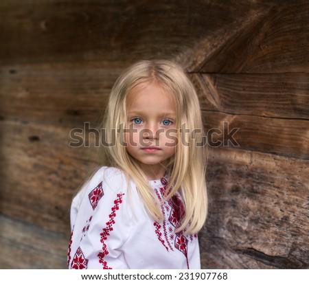 Wonderfull little blonde girl in ukrainian national costume - close up portrait - stock photo