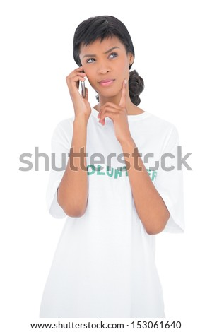 Wondering black haired volunteer calling someone with her mobile phone on white background - stock photo