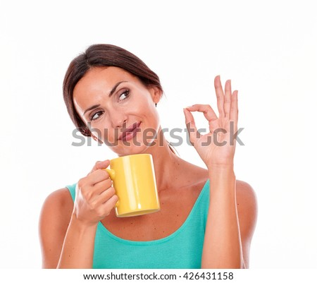 Wondering brunette woman with coffee mug looking away gesturing a perfect sign and wearing a green tank top and her long hair tied back isolated - stock photo