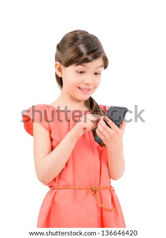 Wondering little cute girl in red dress surprised with an interesting information on mobile smartphone. Isolated on white background - stock photo