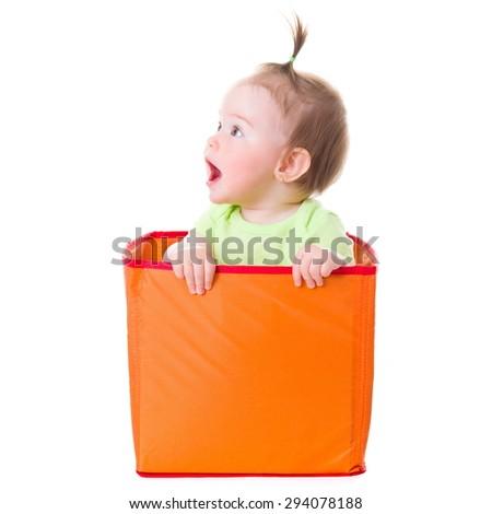 Wondering pretty baby girl sitting in orange box - stock photo
