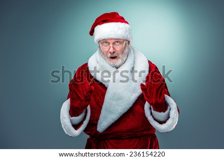 Wondering Santa Claus in glasses with a gray beard and raised arms on a blue background