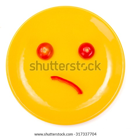 Wondering smiley face made on yellow plate with tomato and pepper slice - stock photo