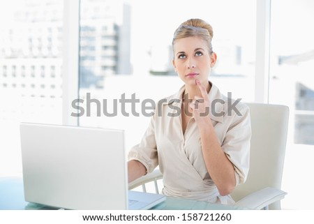 Wondering young blonde businesswoman using a laptop at office
