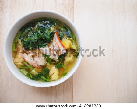 Wonton with soup on wood background