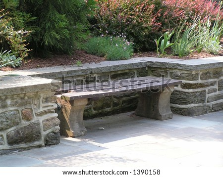 wood and concrete bench set in a niche along a stone retaining wall with garden behind