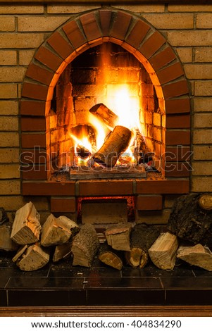 wood and fire in fireplace in country cottage - stock photo