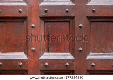 Wood and metal door with metallic spikes looking worn and grungy.  - stock photo
