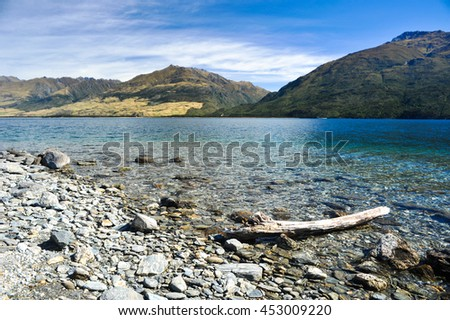 Wood and rock on the beach at Lake Wanaka, New Zealand - stock photo