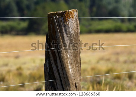 wood and wire fence in the green fields, with fog in the valley - stock photo