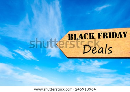 Wood arrow sign against clear blue sky with Black Friday Deals message, Sales conceptual image - stock photo