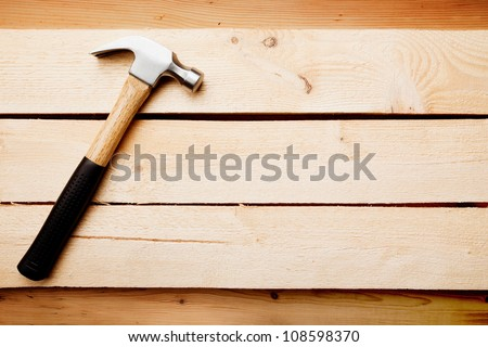 Wood background with a hammer, home improvement concept - stock photo