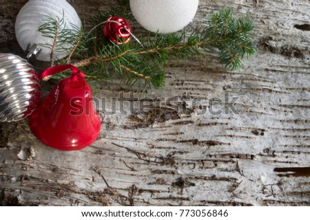 Wood bark background with christmas decoration, pine branch, balls and bells