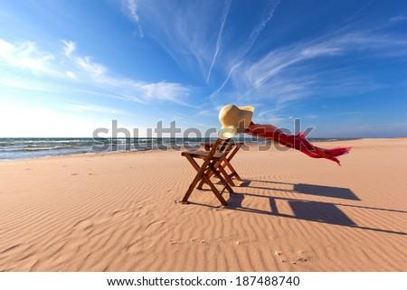 Wood Beach Chair and Beach Hat on Beach - stock photo