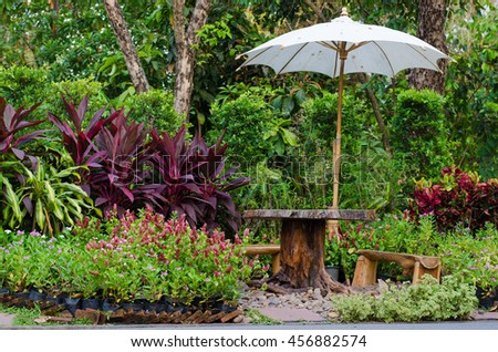 wood bench and table with white umbrella among flower in park, natural style, relaxing corner