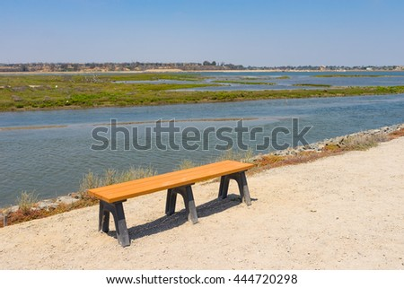 Wood bench on water edge and sandy park trail. - stock photo