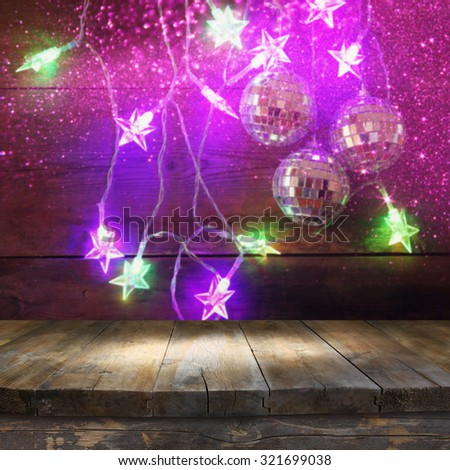 wood board table in front of Christmas colorful gold garland lights on wooden rustic background. filtered image. selective focus. glitter overlay  - stock photo