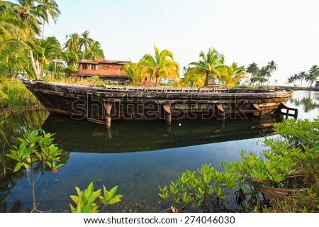 Wood boat is landing near the shore of the pond - stock photo
