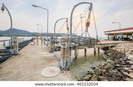 wood boat on davits and cement jetty - stock photo