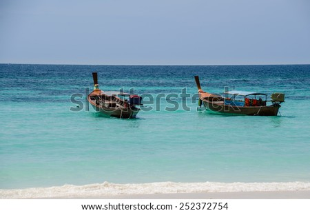 Wood boats on turquoise color sea with clear sky , Andaman sea , Thailand. - stock photo