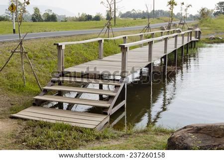 wood bridge cross the canal. - stock photo