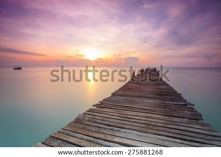 Wood bridge on the sea  between sunrise - stock photo
