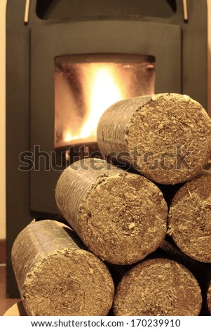 Wood briquettes for stoves background with fire - stock photo