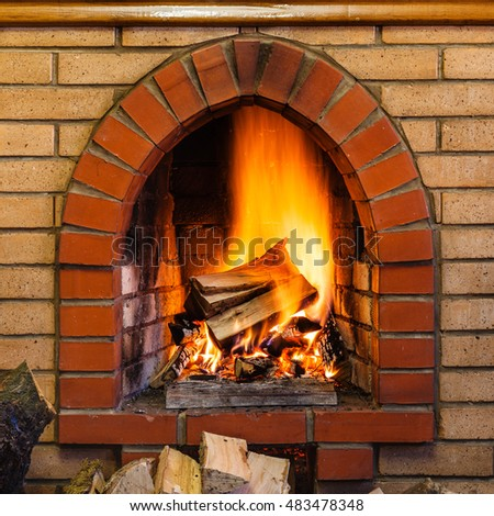 wood burning in indoor brick fireplace in country cottage