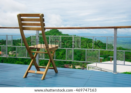 wood chair beside the rail balcony