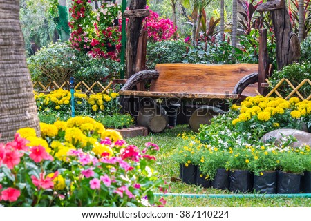 Wood chair in the flowers garden./ Flowers in the garden. - stock photo