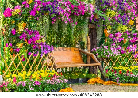 Wood chair in the flowers garden on summer./ Wood chair in the flowers garden. - stock photo