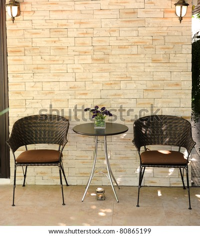 wood chair on a rock wall. - stock photo