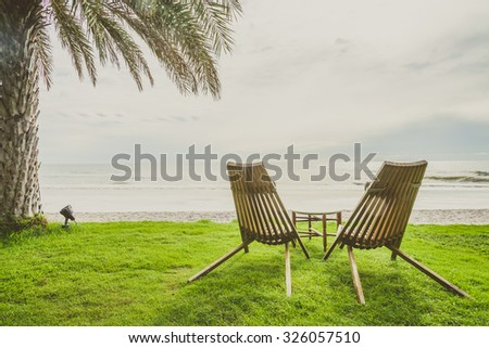 Wood chair on the green grass with beach and palm tree background - vintage filter