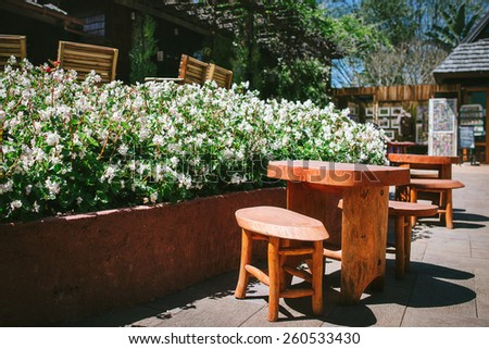 wood chairs and table in the flower garden - stock photo