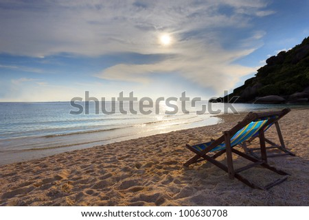 wood chairs beach at sea side and sun set - stock photo