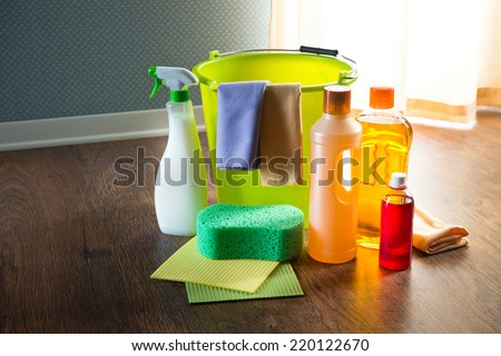 Wood cleaners and detergents on floor with bucket, gloves, cloth and sponges. - stock photo