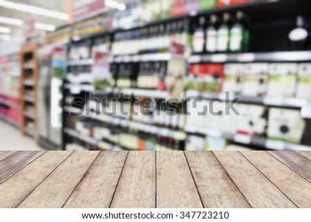 wood counter product display with wine shelves in supermarket blurred background - stock photo
