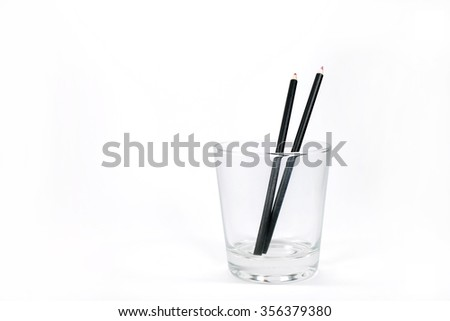 Wood crayon in glass on white background