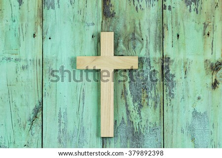 Wood cross hanging on antique rustic mint green wooden background - stock photo