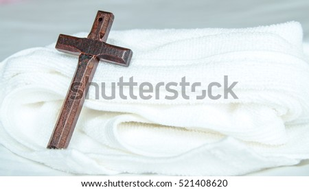 wood cross on white bed