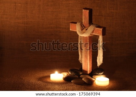 Wood cross with cloth by candles and stones by burlap background - stock photo