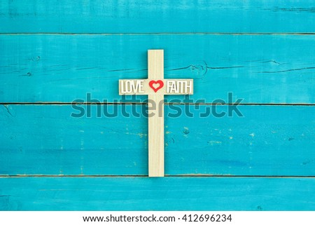 Wood cross with red heart, FAITH and LOVE on antique rustic teal blue wooden background - stock photo