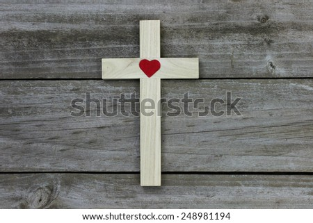 Wood cross with red heart on rugged wooden background - stock photo