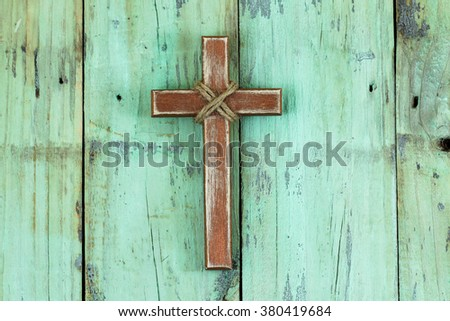 Wood cross with rope hanging on antique rustic mint green wooden background - stock photo
