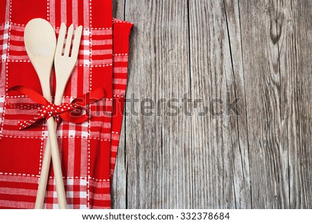 wood cutlery and checkered napkin on wooden table - stock photo