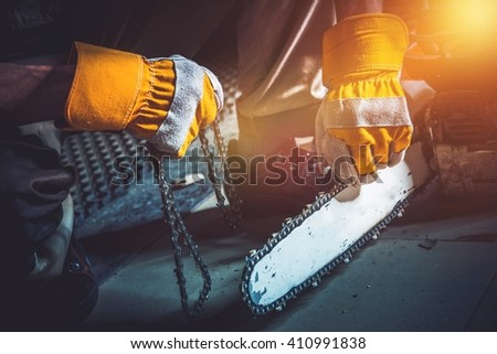 Wood Cutter Old Chain Replacing by New One. Taking Care of Equipment. - stock photo