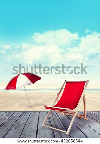 Wood deck with beach chair and ocean in background  - stock photo